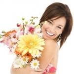 Радостная девушка с прижатыми к груди цветами