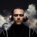 Мужчина слушает музыку в наушниках, из которых летят искры и валит дым
