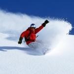 Мужчина на сноуборде скатывается с белоснежной горы