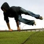 Парень в капюшоне перепрыгивает через забор