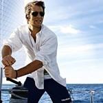 Мужчина в солнцезащитных очках управляет парусной яхтой