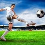 Футболист в светлой форме пинает по мячу на футбольном поле