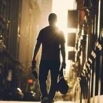 Силуэт парня со спины, который идёт по городу