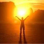 Силуэт человека с поднятыми руками на фоне солнца