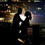 Силуэты девушки и парня на фоне крупного города с небоскрёбами ночью