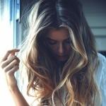 Девушка с длинными волосами и опущенной вниз головой