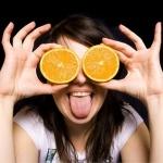 Девушка с двумя половинками апельсина на месте глаз и высунутым языком