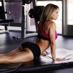 Девушка тренируется в спортзале на мате