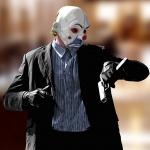 Джокер в клоунской маске смотрит на пистолет