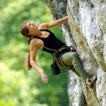 Картинка со спортивной девушкой карабкающейся по отвесной скале