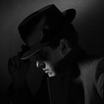 Чёрно-белая картинка с парнем в шляпе и пальто.