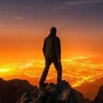 Силуэт мужчины на горе на фоне ночного города
