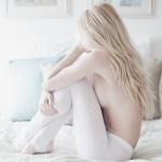 Блондинка топлес в белых колготках отвернувшись сидит на кровати