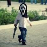 Вооружённый автоматом мальчик в маске гуляет по улицам