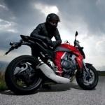 Мужчина стоит облокотившись на спортивный мотоцикл