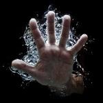 Рука с расставленными пальцами в воде
