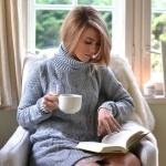 Девушка в кресле читает книгу с кружкой в руке