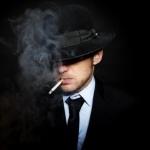 Мужчина в шляпе с сигаретой во рту