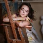 Перепачканная красками девушка сидит возле мольберта с закрытыми глазами