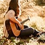 Девушка с акустической гитарой сидит на земле