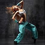 Танцующая с улыбкой девушка в топике спортивных штанах