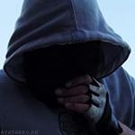 Мужчина в капюшоне с держит руку у скрытого в тени лица