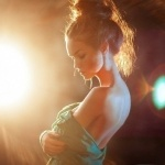 Девушка с волосами, собранными в пучок стоит на фоне прожектора