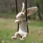Игрушечный заяц из шерсти на качелях