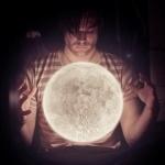 Мужчина со светящейся луной между рук