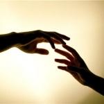 Тянущиеся друг к другу руки на фоне света
